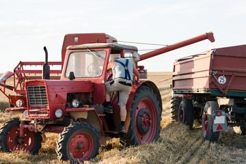 Farmer adjusting combine trailer during grain harvest