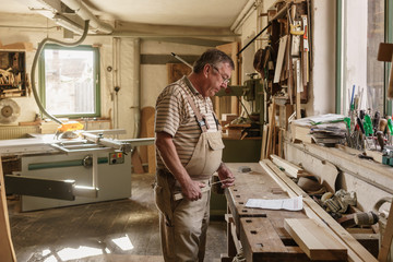 Craftsman in his wood workshop holding  folding rule and studyin