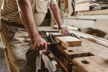 Craftsman in his carpentry workshop pressing wooden workpiece wi