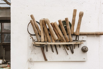 Shelf with used vintage chisels attached to wall in carpentry