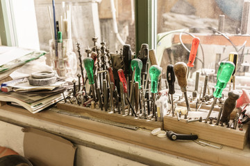 Quite messy shelf in wood workshop with screwdrivers and other tools