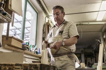 Carpentry master in workshop hammering wooden dowels into boards