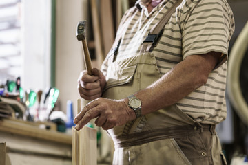 Craftsman in carpentry workshop pounding in wooden pegs into boards
