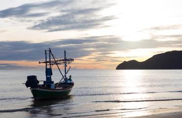fishing boat in a morning on the beach sunrise