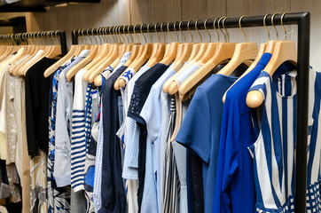 Multi-Colored Women's Clothing On Wooden Hangers. Blouses, Shirts, Trousers, Jackets.