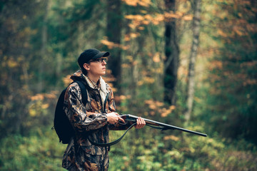 Male hunter in the autumn forest. A man holding a gun. Wall mural