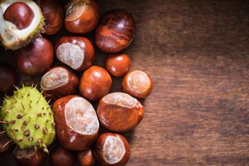 Autumn chestnuts on wooden background