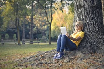Woman using a tablet while sitting under a secular tree