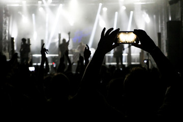 Silhouette of hands recording videos at music concert