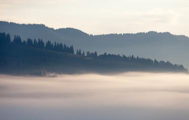 Fog over mountain range in sunrise light.