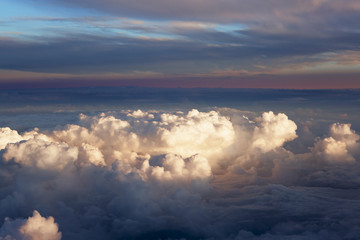 Aerial view of thick clouds over the land, the landscape. The texture of the scenic sky during sunset.