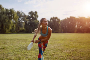 Young athletic girl playing frisbee
