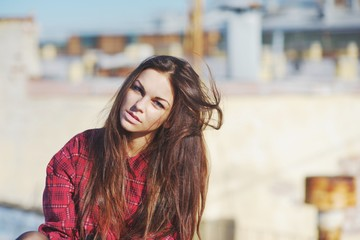 Beautiful thoughtful brunette with long disheveled hair in the wind with blue eyes in a red plaid shirt on a blurred background of city roofs.