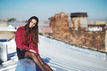 Young pretty girl sitting on a iron roof.
