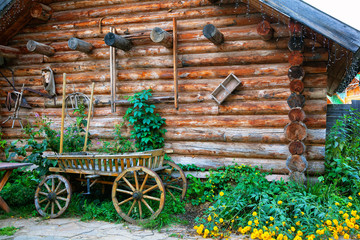 wooden cart on a background of a wooden hut. Country motives