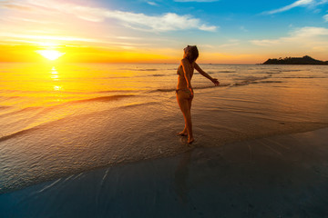 Young woman worth towards the beautiful sunset on the sea beach.