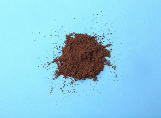 Ground roasted coffee on blue background