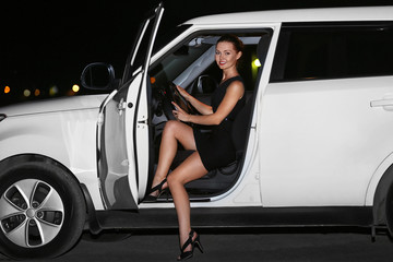 Beautiful young woman getting out of car