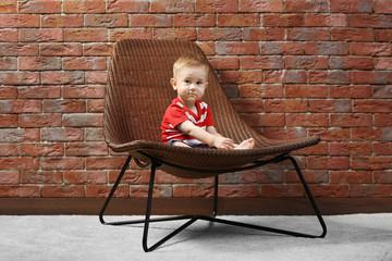 Cute baby boy sitting in a designer chair on a brick wall background