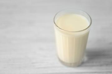 Glass of fresh milk on light blurred background