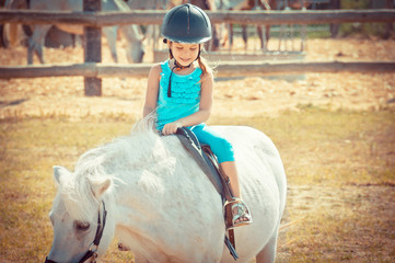 Lovely girl on a horse. Child and animal. Litlle girl riding.