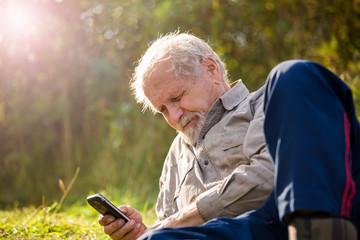 Пенсионер с мобильным телефоном на природе