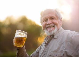 Пенсионер пьет пиво на природе