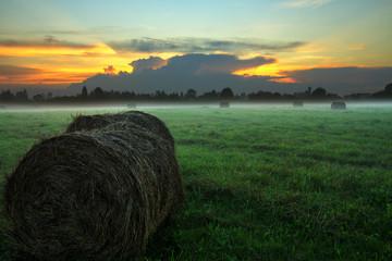 Туманный закат в поле со стогами сена