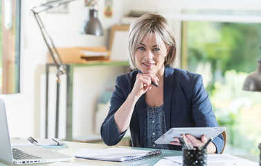 a middleage woman sitting at her desk working with a tablet