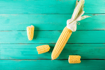 Corn cobs on turquoise wooden background