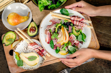 Woman hands holding plate with fresh salad.
