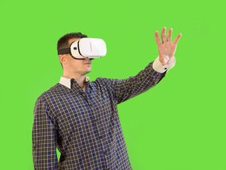 Man Reaching Out with Virtual Reality Goggles by Green Screen