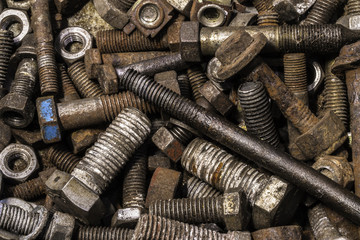 Selection of old rusty  nuts and bolts in container