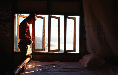 man standing inside a room overlooking the mountains