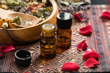 essential oils with dried herbs and roses
