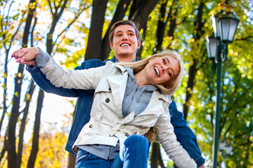 Young couple hugging and flirting in autumn park and looking up. Man hugging his girlfriend's shoulders in autumn park.