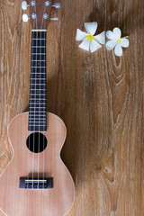 Ukulele on wooden background with white flowers