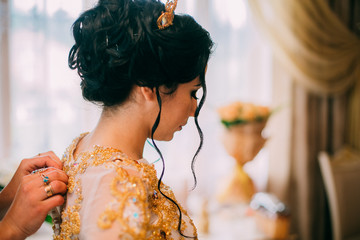 Close up portrait of pretty bride in hotel room. Woman in white dress decorated yellow beads. Girl in yellow golden crown. Luxury wedding day.