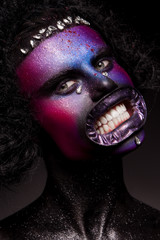Clown and Halloween theme: Scary clown with black hair and gems, on a dark background in the studio
