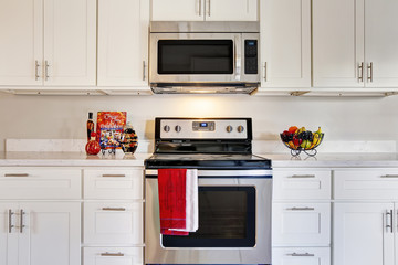 Bright kitchen room with steel appliances and granite tops