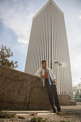 Handsome, white and strong business man posing in photos of business and fashion theme on the street. He has unbuttoned shirt and the background is the Picasso Tower in the center of Madrid, Spain.