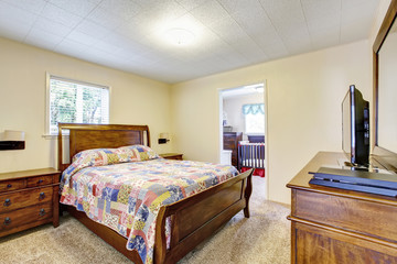 Wooden furnished bedroom interior with nice bedding and TV set