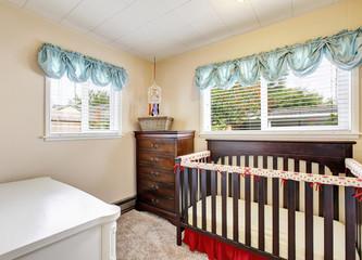 Cherry wood baby crib in nursery interior with carpet floor.