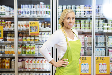 Female Worker Standing With Hands On Hip In Grocery Store