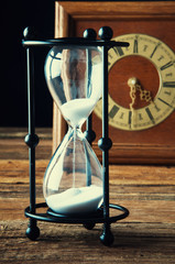 Hourglass and old vintage clock
