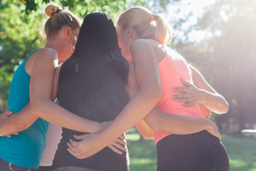 Sports women embracing together