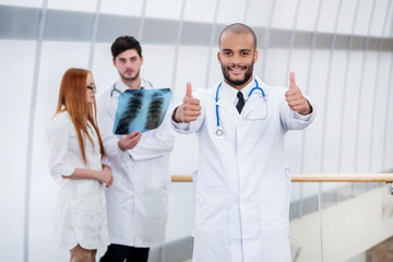 Portrait of a successful doctor showing two thumbs up. Three con