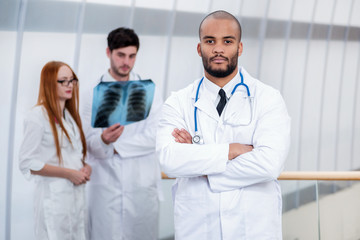 Portrait of a serious doctor with arms folded. Two confident doc