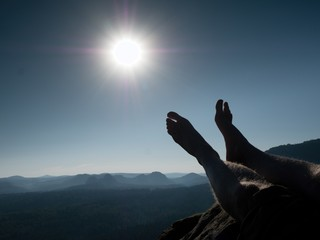 Naked male legs take rest on peak. Outdoor activities