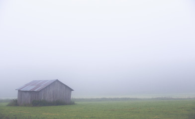An old barn on a foggy morning in Finland. Image has a vintage effect applied.
